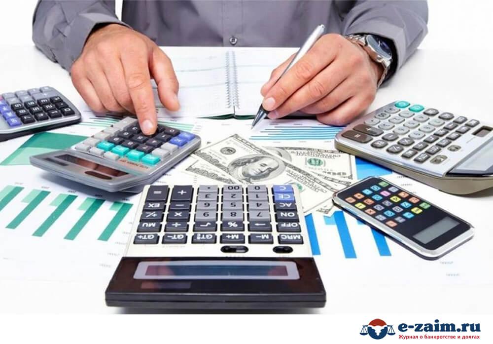 Калькуляторы, деньги и мужская рука с ручкой